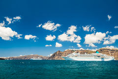 Big cruise liners near the Greek Islands. Bright turquoise sea and blue sky. Santorini island, Greece Royalty Free Stock Photos