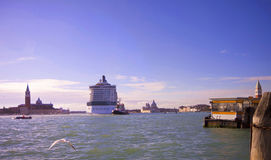 Big cruise ship cross Venice to Giudecca Canal. Big cruise ship crosses Grand Canal near S. Marco, towering over the belfries of the churches in Venice Royalty Free Stock Photo