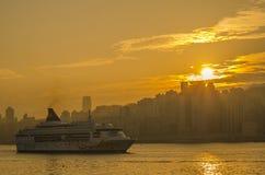 Big Cruise Ship departed from Ocean Terminal and drove across Victoria Harbor. HONG KONG - DECEMBER 7 2016 : Big Cruise Ship departed from Ocean Terminal and stock photos