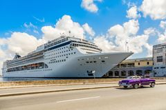 Big cruise ship docked in port of Havana and road with retro old Stock Image