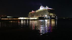 Passenger a big cruise ship with lighted lights stands in the port at night stands at the pier. Big cruise ship with lighted lights stands in the port at night stock video footage