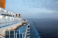 Big cruise ship riding in evening. light on. Few of people on deck Stock Image