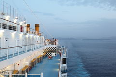 Big cruise ship riding in evening. light on. Few of people on deck of cruise ship Royalty Free Stock Photography
