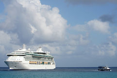 Big cruise ship and small boat stock photography