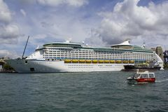 Big cruise ship in sydney harbour and small touristic boat passing stock photo