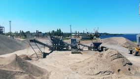Big crushing machine works at a quarry near water. Industrial mining concept.