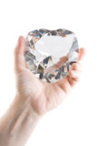 Big crystal heart in men's hand. On the white background Royalty Free Stock Photography