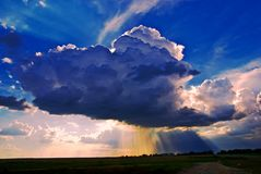 Big cumuli cloud with sun rays. And rain against blue sky Stock Images