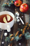 Big cup of black tea, red apples and pine branches Stock Images