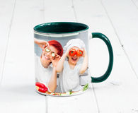 Big cup with dark green handle. Big green cup with dark green handle and print of a kids cooking something Stock Photography