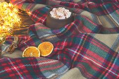 Big cup of hot cocoa with marshmallow, cinnamon and dry orange and warm blanket on an old vintage wooden and Christmas light. Cozy Royalty Free Stock Image