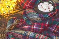Big cup of hot cocoa with marshmallow, cinnamon and warm blanket on an old vintage wooden and Christmas light. Cozy christmas or a. Utumn arrangement Stock Photos