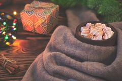 Big cup of hot cocoa with marshmallow, gift box, cinnamon and warm blanket on an old vintage wooden and Christmas light. Stock Photo