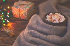 Big cup of hot cocoa with marshmallow, gift box, cinnamon and warm blanket on an old vintage wooden and Christmas light. Royalty Free Stock Photo
