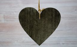 Big dark wooden heart on the light wooden background. Close up and big copyspace for your text royalty free stock photography