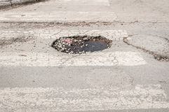 Big deep dangerous pathole in the middle of the asphalt road, danger for cars driving can cause an accident or breakdown of vehicl. E Royalty Free Stock Images