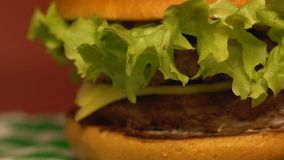 Big delicious double cheeseburger on table in fast food restaurant, close up. Stock footage stock video