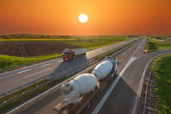Big delivery trucks on the empty highway at sunset Royalty Free Stock Image