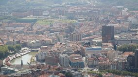 Big dense city lying at bottom of old green mountains, vertical panorama view. Stock footage stock video footage