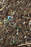 A huge deposit of debris polluting the water surface. A big deposit of wood and plastic bottles and debris floating on water surface Stock Images