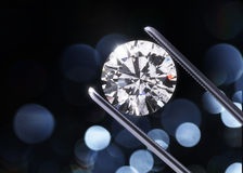 Big diamond in tweezers. Luxury diamond in tweezers closeup with bright bokeh background royalty free illustration