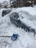 The Big Dig - 2015. Shoveling snow off a parked car on a Boston city street after the blizzard Stock Image