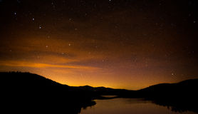 Big dipper. The big dipper hangs in the summer sky over the Wrightsville Reservoir in Middlesex Vermont. In the background, the sky is lit up by the distant town royalty free stock photo