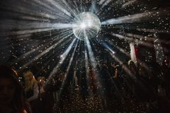 A big disco ball is hanging from the ceiling. A lot of people are dancing on the background royalty free stock photography