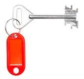 Big door key with red blank key chain isolated. On white background Royalty Free Stock Photography