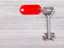 Big door key with red key chain on wooden board. Big door key with red blank key chain on wooden board Stock Image