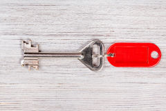 Big door key with red keychain on wooden table. Big door key with red blank keychain on wooden table Royalty Free Stock Photos