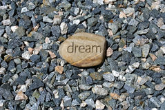Big dream on small rocks. A big dream rock stands out among smaller stones, a rock with the word dream inscribed in it Royalty Free Stock Photo