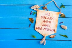 Big dreams have small beginnings text on Paper Scroll. Big dreams have small beginnings text on Canvas Paper Scroll with dried flower around and blue wooden royalty free stock image