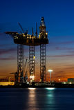 Big drilling platform in dock. Big drilling platform in repair in the harbour at sunset Royalty Free Stock Photo