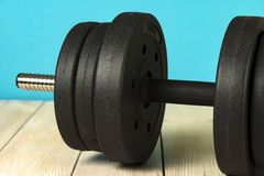 Big dumbbell on a colored background. Sports equipment and inventory royalty free stock photos