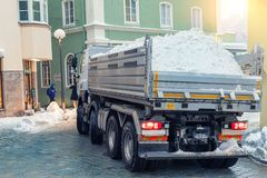 Big dump truck fully loaded with snow driving through narrow street of historical center at old european city. Heavy machinery