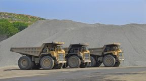 Big dump trucks. Three 85 ton capacity Caterpillar dump trucks at stone quarry. This is a cropped version Stock Photo