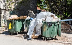 Big dumpster garbage cans full of overflow litter polluting the street in the city with junk and trash.  royalty free stock image