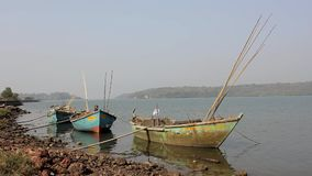 Big empty old battered fishing boats anchored off the riverbank. A big empty old battered fishing boats anchored off the riverbank stock footage