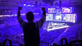 Big esports event. Happy dedicated fan of video games at arena. Cheering with a hands raised.