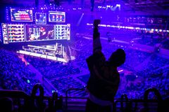 Free Big Esports Event. Video Games Fan On A Tribune At Tournament`s Arena With Hands Raised. Cheering For His Favorite Team. Royalty Free Stock Images - 160802909
