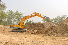 A big excavator earthmoving works on new construction site Royalty Free Stock Images