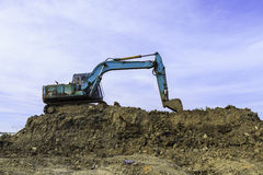 Big excavator on new construction site. In the background the blue sky and sun Stock Image