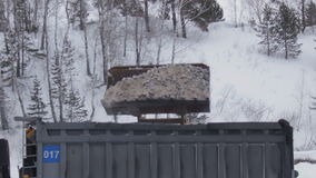 Big excavator`s bucket loads rocks to dumper truck in a quarry opencast. Mining industry, geology. Winter season. Big excavator`s bucket loads rocks to dumper stock video