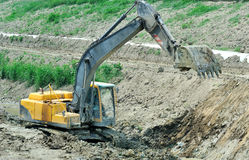 Big excavator working on the river bed Stock Photos