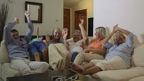 Big excited family watching sport game on TV. Slow motion clip of a big family spending evening in front of TV at home. They watching sport game and getting stock footage