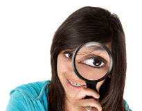 Big Eye. Young girl looking through a magnifying glass Stock Photography