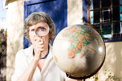 Big eye with magnifying glass. This attractive lady is planning her vacation, using a magnifying glass royalty free stock photo