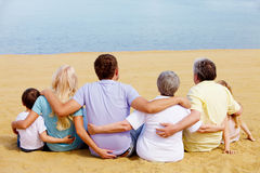 Big family. Backs of serene family members sitting on sandy shore in front of blue water Royalty Free Stock Photography