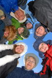 Big Family. A big family dressed in warm winter clothes standing in a circle and looking down royalty free stock photo
